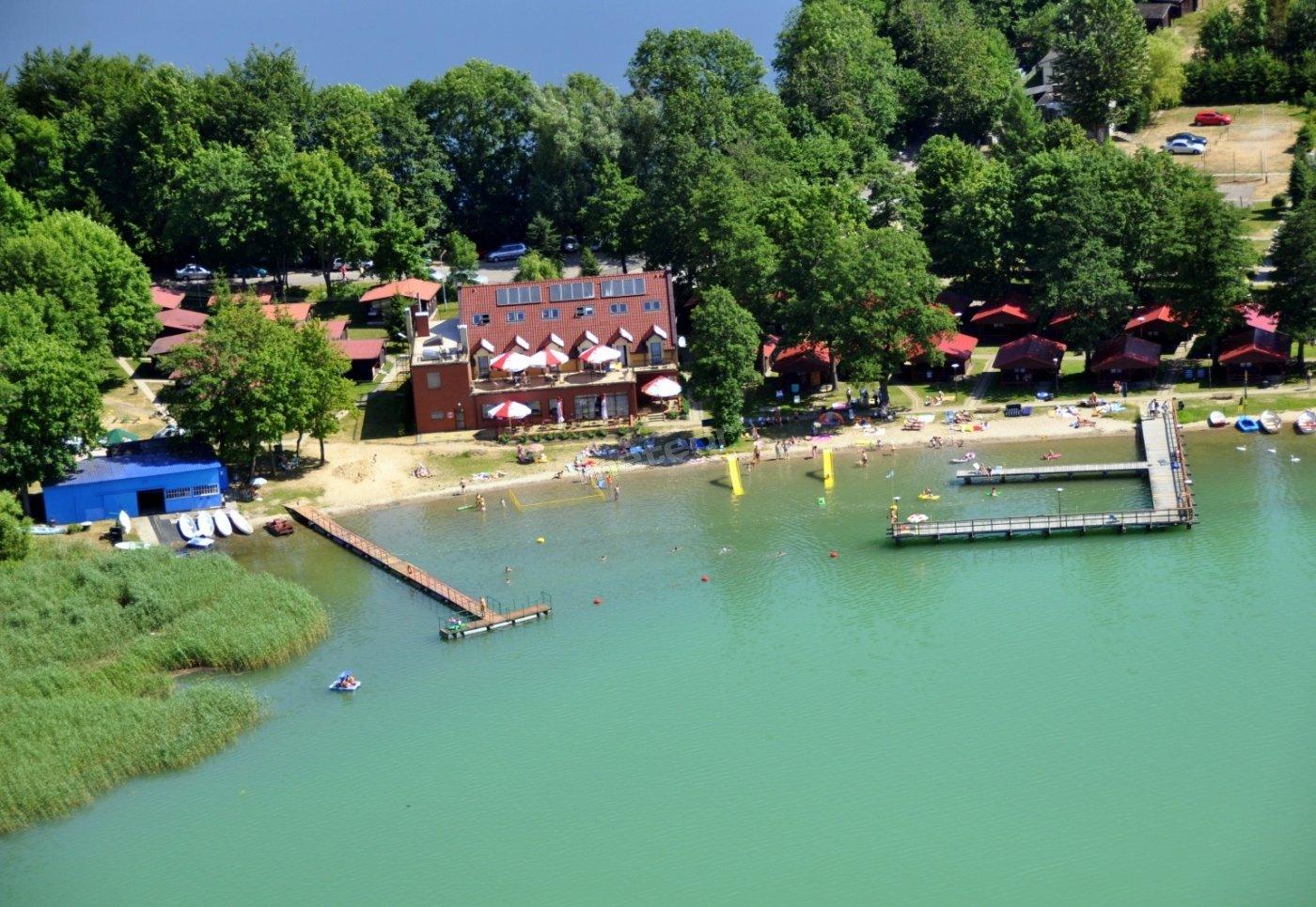 Widok na kąpielisko ośrodka, budynek główny ze stołówką i salą szkoleniową oraz domki 2-osobowe.