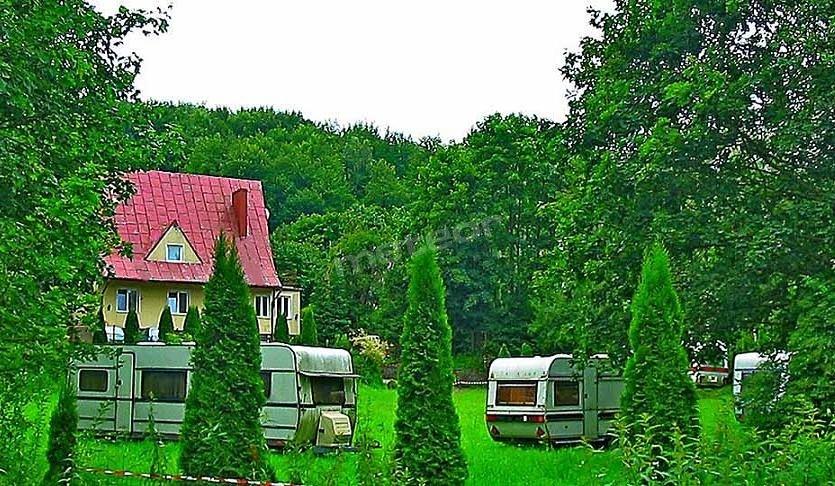 Dom z apartamentami oraz przyczepy tonące w zieleni.