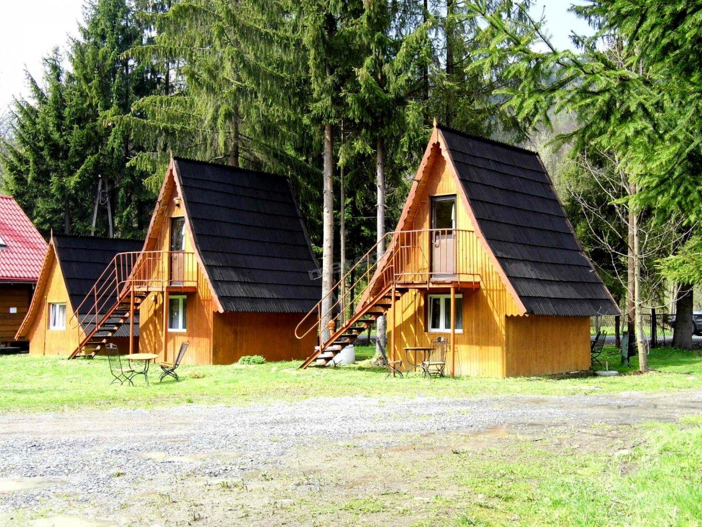 Widok na drewniane domki od strony zielonego placu z boiskiem do siatkówki.