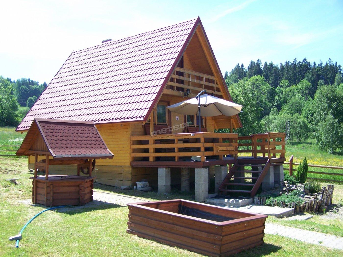 Duży taras z meblami ogrodowymi ( stół, ławki, masywne krzesła, duży parasol)