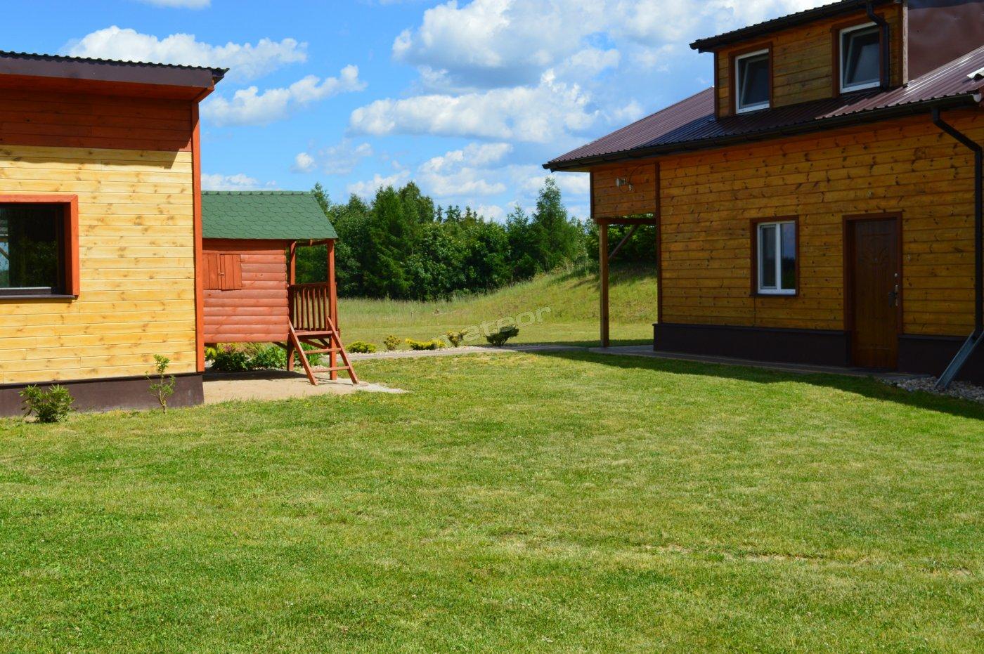 Po prawej: budynek agroturystyczny, po lewej: plac zabaw dla dzieci, sauna, salka ze stołem